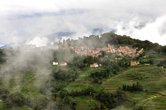 Small town above clouds and terraced fields. A small town in the mist, looks like above clouds and terraced fields royalty free stock photos