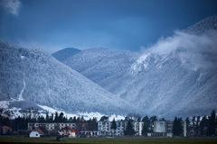 Town by the mountains. Small town at the bottom of the mountains in winter Royalty Free Stock Photo