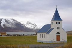A small Christian church in a field with beautiful snowy mountains in the background stock photos