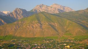 Small town at the foot of the mountain. On the sunset.. Drone camera stock video footage