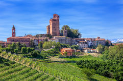 Small town and green vineyards in Piedmont, Italy. Small town with medieval castle and green vineyards on downhill in spring in Piedmont, Northern Italy Royalty Free Stock Photo