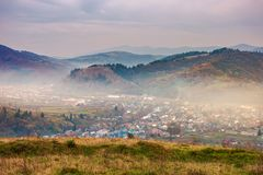 Small town in hazy valley on gloomy afternoon. Autumn countryside in mountains. small town in hazy valley. forested hills in fall colors. gloomy afternoon with royalty free stock image