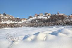 Small town on the hill covered by snow. Piedmont, Italy. Royalty Free Stock Image