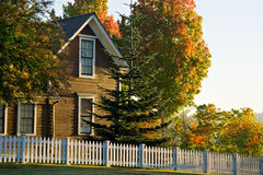 Small town home white picket fence. Quaint small town home surrounded by classic white picket fence and autumn trees Royalty Free Stock Photos