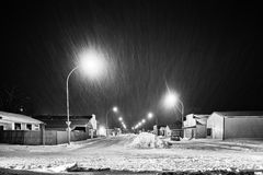Small town main street. A long line of snow plowed down the centre of small town main street lined with stores at night in black and white Royalty Free Stock Photos