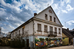 Small town main street. Of Tukums, Latvia. Abandoned building with colourful painting on it. Result of shrinking population. Nice blue sky and clouds in the Stock Image
