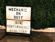 Small town mechanic on duty sign on a sidewalk royalty free stock image
