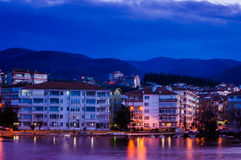 Small Town On The Seaside. Small town next to the seaside with hills and mountains on the background and clouds in the evening sky. A natural and urban landscape Stock Photos