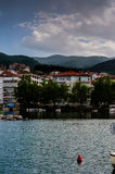 Small Town On The Seaside. Small town next to the seaside with hills and mountains on the background and clouds in the evening sky. A natural and urban landscape Royalty Free Stock Photos