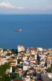 Small town at seaside and ship in sea Royalty Free Stock Images