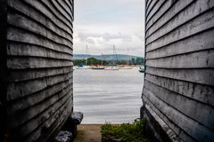English country sea side with boats and mountain view. A small town on seaside where people can sail their boats on weekends. A look through wooden boat house Royalty Free Stock Image