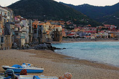 A small town on the shore of the sea. Sea waves almost beat against the walls of houses. Cefalu. Sicily. Italy Stock Photos