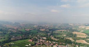 A small town in a valley between green hills, a view from above, a house near a small town, a house on a hill, panoramic. Shooting of a city standing in a stock footage