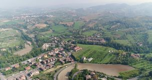 A small town in a valley between green hills, a view from above, a house near a small town, a house on a hill, panoramic. Shooting of a city standing in a stock video footage