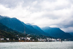 Small town at Yangtze river`s edge with mountain and cloud background Stock Photos