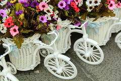 Small toy bicycle with flowers in a basket on  cobblestone street. Postcard Greetings Royalty Free Stock Photos