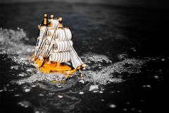 Small toy boat in the water with big waves. Black and white stock images