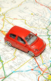 Small Toy Car On Road Map. A small red toy car on a paper road map Stock Photos