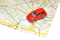 Small Toy Car On Road Map. A small red toy car on a paper road map Stock Photography