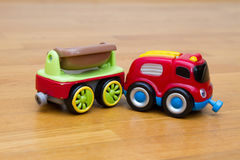 Small toy car with a trailer. Child boy toddler playing with toy car indoors Royalty Free Stock Photos