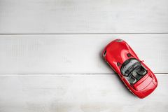 Small toy car on a white wooden background. Top view. Copy space Royalty Free Stock Photo