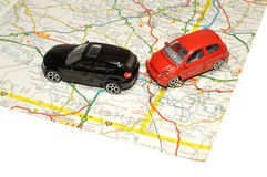 Small Toy Cars On Road Map. Two small red and black toy cars on a paper road map Stock Images