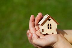Small toy house in hands of child on green grass background. Concept mortgage, dream house, real estate acquisition. In frame only hands, without face . Soft royalty free stock photos