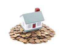 Small toy house on a pile of coins Royalty Free Stock Photo