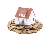 Small toy house on a pile of coins Stock Photo