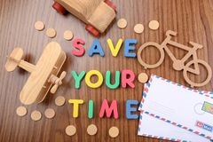 Small toy transport and phrase \'Save your time\' composed from letters on wooden table royalty free stock photography