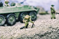 Small toys of soldiers and military equipment. A staged model of the fighting.  stock image