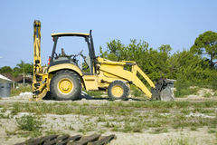 A small tractor with backhoe and blade Royalty Free Stock Photography