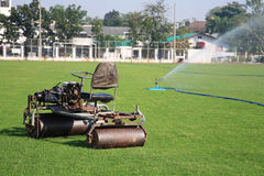 Small tractor cutting grass  at soccer or football field Royalty Free Stock Image