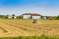 Small tractor plowing a large field Stock Photography