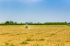 Small tractor plowing a large field Royalty Free Stock Image
