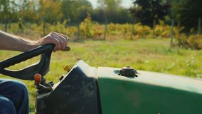 Machines on the farm. Close-up of hands on the handlebars of a small tractor, driving through a field or vineyard. Small tractor rides across the field in the stock video