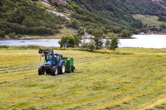 Small tractor with round baler haymaking on a field in Geiranger, Norway.  royalty free stock photos