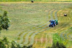 Small tractor with round baler haymaking on a field in Geiranger, Norway.  stock photo