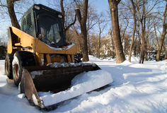 Small tractor with snowplough covered in snow in the park Royalty Free Stock Photos