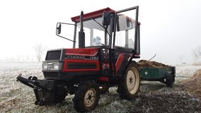 Small tractor on the winter field. Small red  tractor with trailer on the winter field. Yanmar FX18D Super forte fertilizer horse-droppings Stock Photos