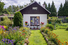 Small traditional cottage cabin with flower garden bed Royalty Free Stock Photos