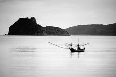 Small traditional fishing boat alone on the sea in black and white picture style Stock Photos