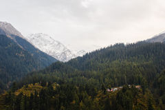Small traditional village in himalayan mountains covered with forest and snow Royalty Free Stock Photo