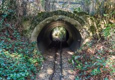 Small train railway with a tube tunnel and some generic vegetation. A small train railway with a tube tunnel and some generic vegetation royalty free stock photo