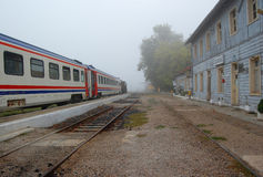 Small train station in foggy morning Stock Images