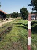 Small train station on narrow gauge. Village train station. Railroad tracks, railway traffic signs. Royalty Free Stock Image