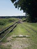 Small train station on narrow gauge. Village train station. Railroad tracks, railway traffic signs. Royalty Free Stock Photography