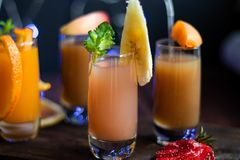 Small transparent glasses filled with different juices. stock image
