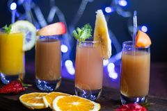 Small transparent glasses filled with different juices. Peach, orange, banana, apricot. royalty free stock images