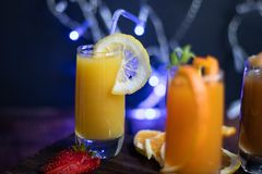 Small transparent glasses filled with different juices. Peach, orange, banana, apricot. royalty free stock image